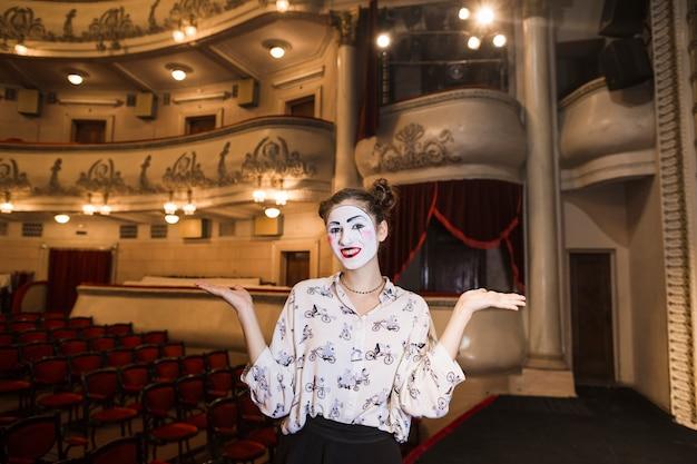 Retrato de mimo femenino de pie en el escenario encogiéndose de hombros Foto gratis