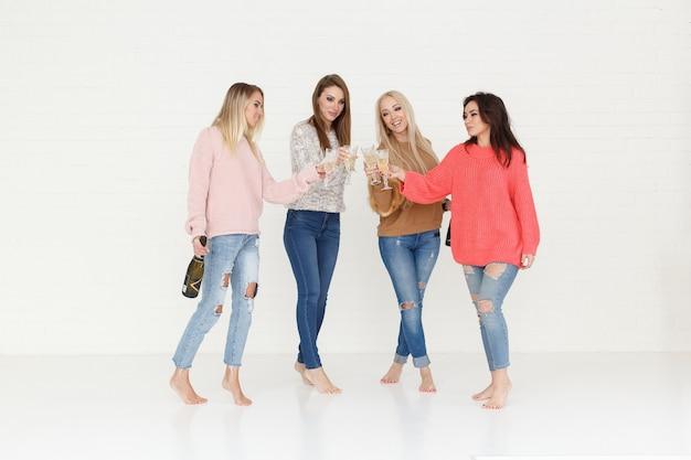 Retrato de moda de cuatro mujeres bebiendo champán y divirtiéndose Foto Premium