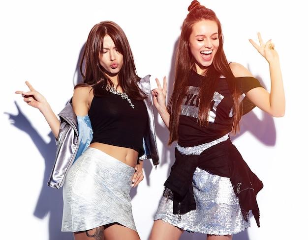 Retrato de moda de dos modelos morenas sonrientes en ropa casual de verano hipster aislado en blanco Foto gratis