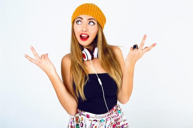 Retrato de moda de hermosa rubia dj hipster chica sosteniendo sus pelos, vistiendo un traje sexy brillante y grandes auriculares blancos. Foto gratis