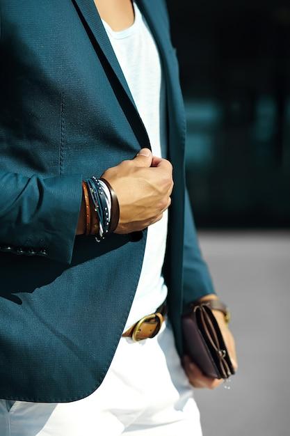 Retrato de moda de joven empresario guapo modelo hombre en traje de tela casual con accesorios en las manos Foto gratis