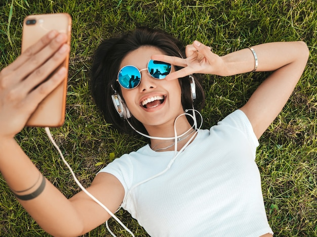 Retrato de moda de mujer joven inconformista elegante tirado en el pasto en el parque. chica teje traje de moda. modelo sonriente haciendo selfie. mujer escuchando música a través de auriculares. vista superior Foto gratis