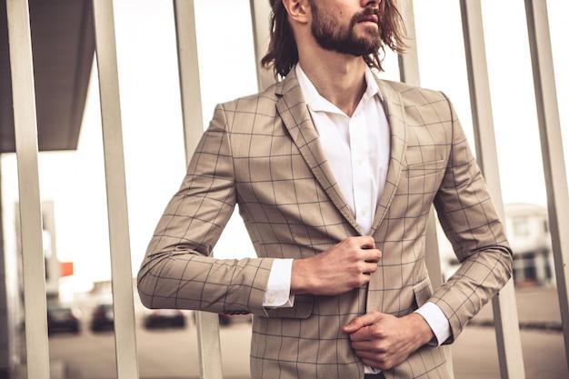 El retrato del modelo atractivo atractivo del hombre de negocios de la moda se vistió en el traje a cuadros elegante que presentaba cerca de la pared de ladrillo en el fondo de la calle. Foto gratis