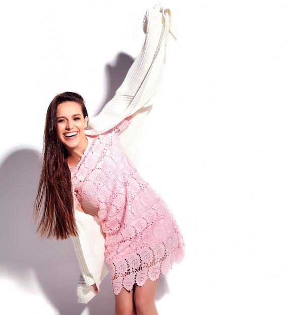 Retrato del modelo caucásico sonriente de la mujer morena hermosa en el vestido elegante del verano rosado brillante aislado en el fondo blanco. celebrando Foto gratis