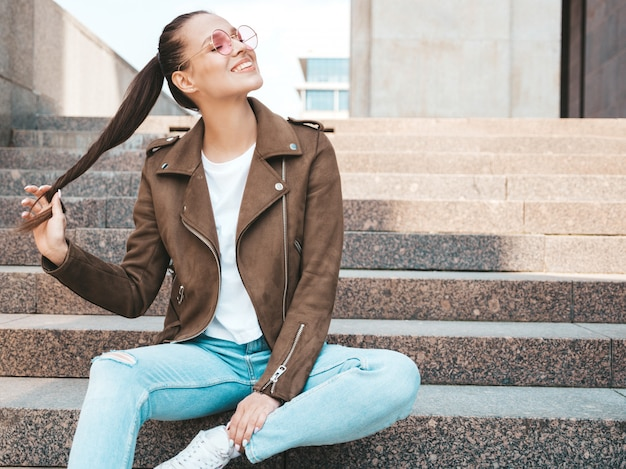 El retrato de la modelo morena sonriente hermosa se vistió en ropa de la chaqueta y de los vaqueros del inconformista del verano. moda niña sentada en pasos en el fondo de la calle. mujer divertida y positiva en gafas de sol redondas Foto gratis