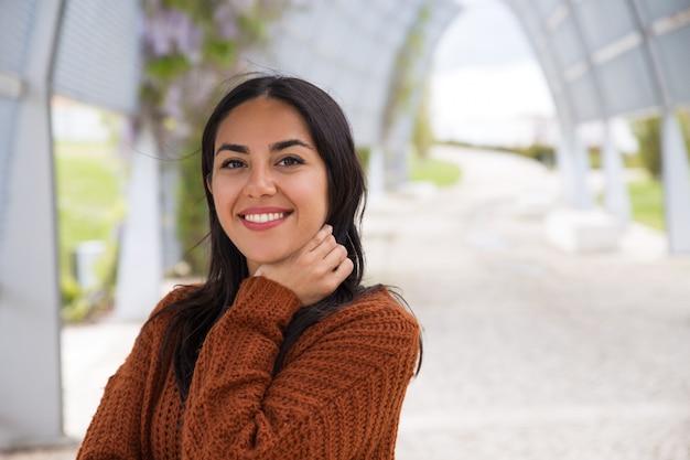Retrato de la muchacha asiática emocionada feliz que ajusta el pelo Foto gratis
