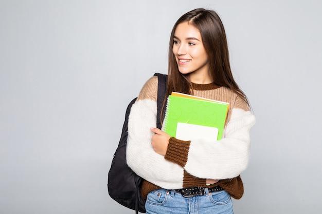 Retrato de muchacha atractiva linda joven estudiante aislada en la pared blanca Foto gratis