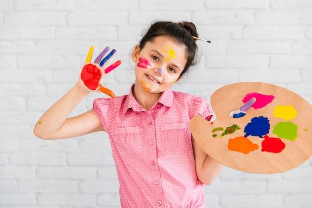 Retrato de una muchacha que muestra sus manos pintadas que sostienen la paleta coloreada multi Foto gratis
