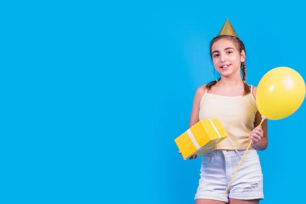 Retrato de una muchacha que sostiene la caja y los globos de regalo en su mano en superficie azul Foto gratis