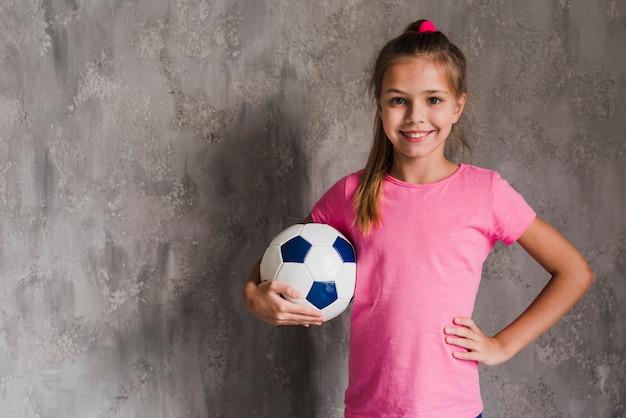 Retrato de una muchacha rubia sonriente con la mano en la cadera que sostiene el balón de fútbol contra la pared gris Foto gratis