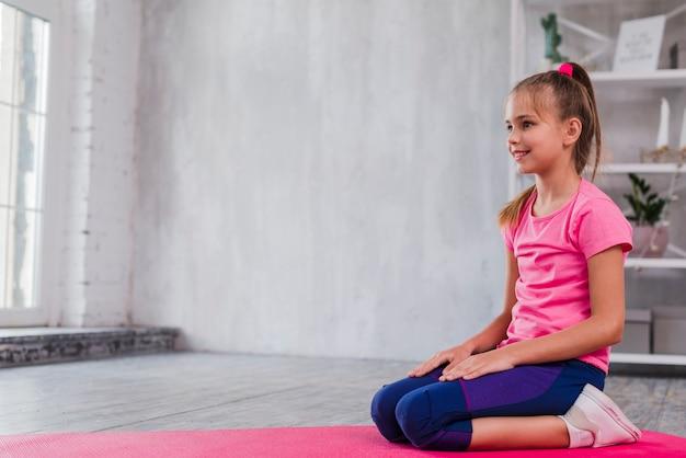 Retrato de una muchacha sonriente que se sienta en la alfombra rosada que mira lejos Foto gratis