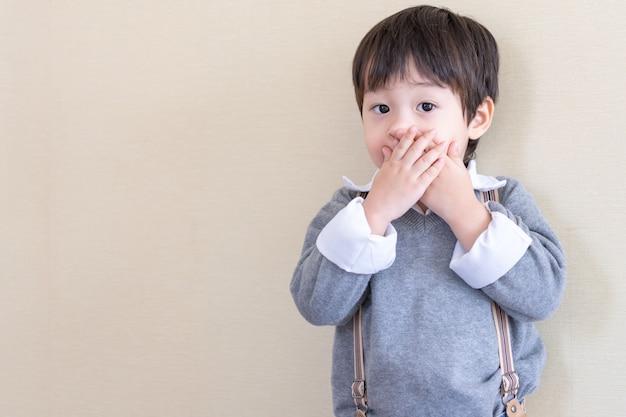 Retrato muchacho asiático de pie y cerró la boca Foto gratis