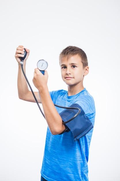 Retrato de un muchacho que mide la presión arterial en el fondo blanco Foto gratis