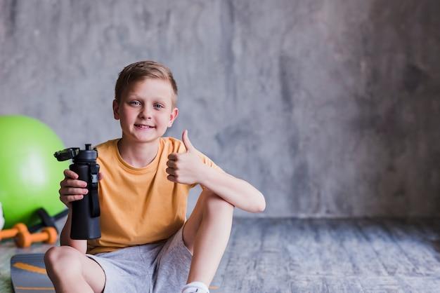 El retrato de un muchacho sonriente que se sienta con la botella de agua que muestra los pulgares sube la muestra Foto gratis