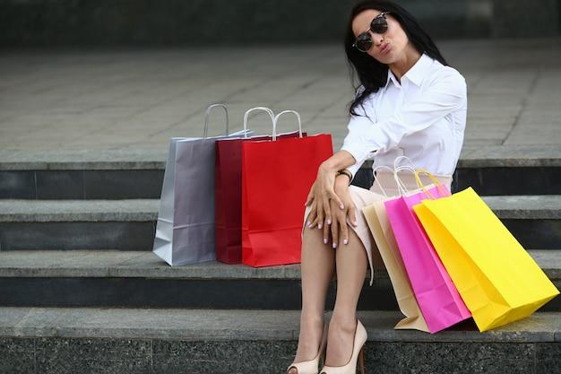 Retrato de mujer alegre que sopla beso en pasos al aire libre. hermosa mujer en elegantes gafas de sol posando con coloridos bolsos de tienda. concepto de moda y compras. Foto Premium