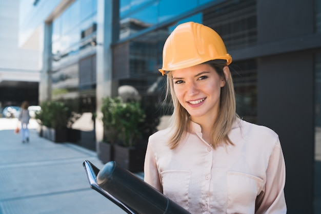 Retrato de mujer arquitecto profesional con casco amarillo y de pie al aire libre. concepto de ingeniero y arquitecto. Foto gratis