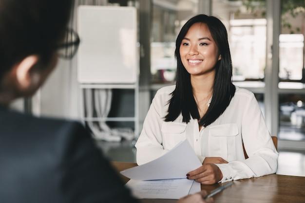 Retrato de mujer asiática alegre sonriendo y sosteniendo un currículum, mientras está sentado frente a la empresaria durante una reunión corporativa o una entrevista de trabajo - concepto de negocio, carrera y colocación Foto Premium