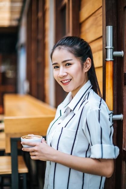 El retrato de la mujer asiática hermosa se relaja en el café Foto gratis