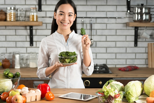 El retrato de la mujer asiática que muestra albahaca verde se va en cocina Foto gratis