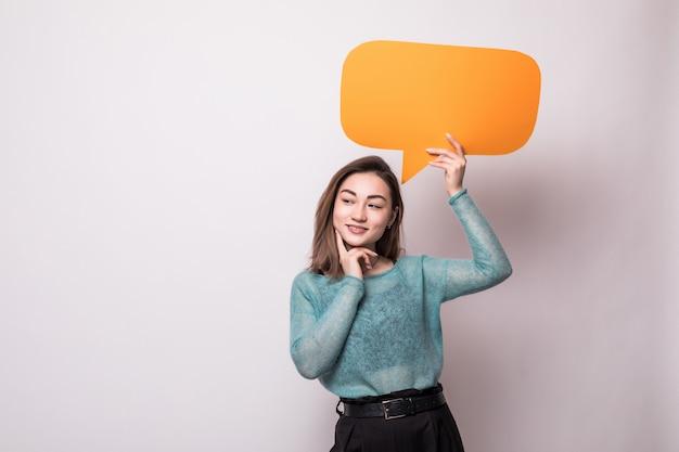 Retrato de una mujer asiática sonriente que sostiene el bocadillo de diálogo anaranjado vacío aislado sobre la pared gris Foto gratis