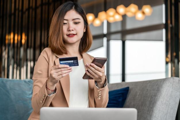 Retrato mujer asiática con tarjeta de crédito con teléfono móvil, computadora portátil para compras en línea en el vestíbulo moderno o espacio de trabajo, taza de café, billetera de dinero tecnológica y concepto de pago en línea, maqueta de tarjeta de crédito Foto Premium