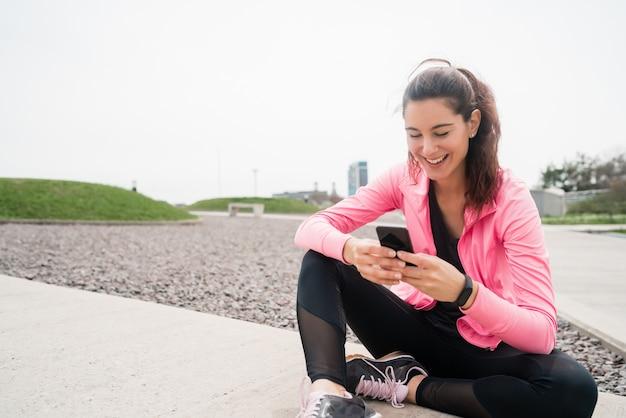 Retrato de una mujer atlética con su teléfono móvil en un descanso del entrenamiento. estilo de vida deportivo y saludable. Foto gratis