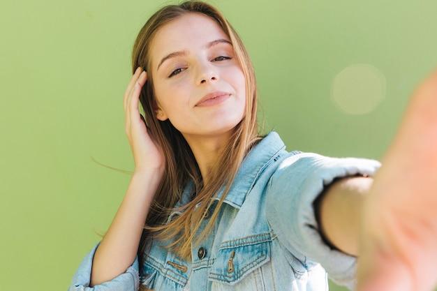 Retrato de una mujer bastante joven que toma el autorretrato en fondo verde Foto gratis