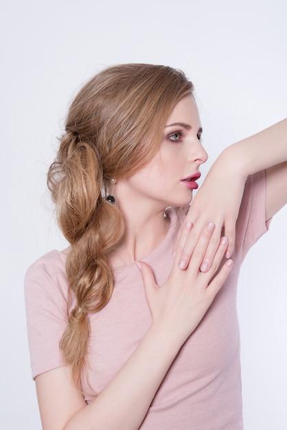 Retrato de mujer de belleza. chica hermosa modelo con piel limpia fresca perfecta y maquillaje profesional. mujer rubia mostrando manicura ideal Foto Premium