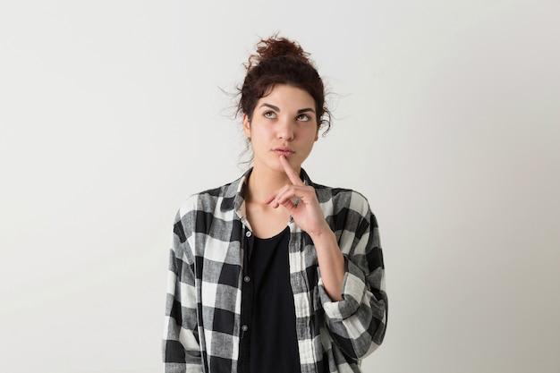 Retrato de mujer bonita joven inconformista en camisa a cuadros pensando, teniendo un problema, posando aislado sobre fondo blanco de estudio Foto gratis