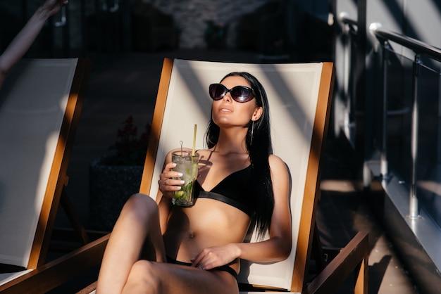 Retrato de mujer con cuerpo en forma de bronceado perfecto con gafas de sol de moda tomando un cóctel Foto Premium