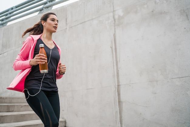 Retrato de una mujer deportiva corriendo en las escaleras al aire libre. conceptos de fitness, deporte y estilo de vida saludable. Foto gratis