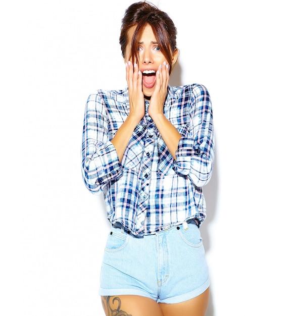 Retrato de mujer elegante en camisa casual a cuadros hipster sin maquillaje en la pared blanca Foto gratis