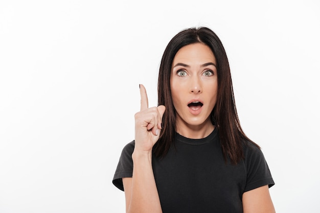 Retrato de una mujer emocionada poiting dedo arriba Foto gratis