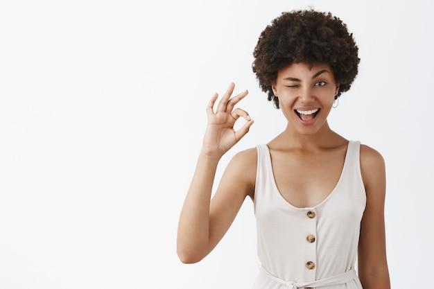 Retrato de mujer emotiva complacida y segura con piel oscura y peinado afro guiñando un ojo con una indirecta y sonriendo mientras muestra un gesto bien Foto gratis