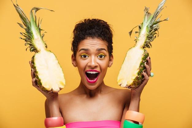 Retrato de mujer encantada de raza mixta con apariencia de moda sosteniendo dos mitades de piña en ambas manos aisladas, sobre pared amarilla Foto gratis