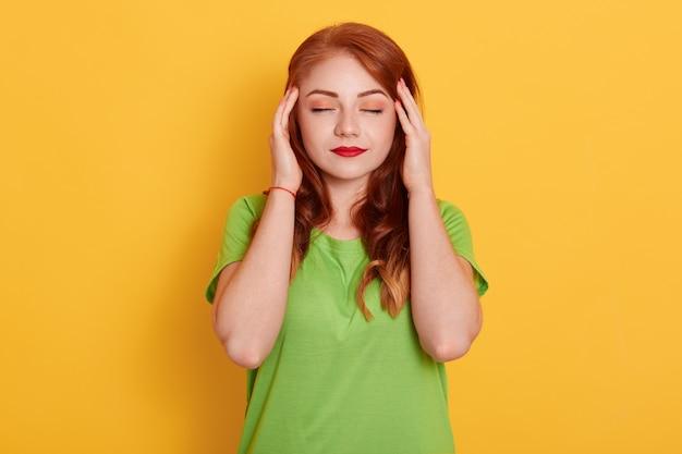 Retrato de mujer encantadora y elegante en camisa verde con dolor de cabeza, tocar las sienes con los dedos y cerrar los ojos Foto gratis