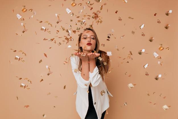 Retrato de mujer encantadora feliz envía un beso en la pared aislada con confeti. feliz celebración de año nuevo, cumpleaños Foto gratis