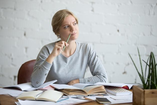 Retrato de una mujer estudiante en el escritorio, frunció el ceño Foto gratis