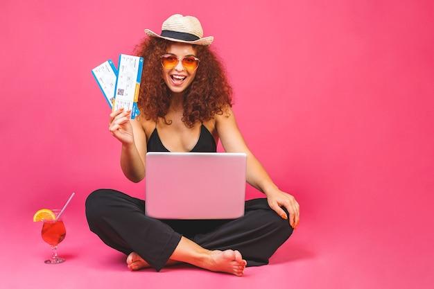 Retrato de mujer feliz en casual sentado en el suelo en posición de loto y sosteniendo un portátil, un cóctel y un billete de avión Foto Premium