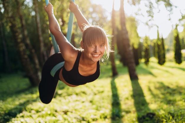 Retrato de mujer feliz haciendo fly yoga en el árbol y mirando a la cámara. Foto Premium