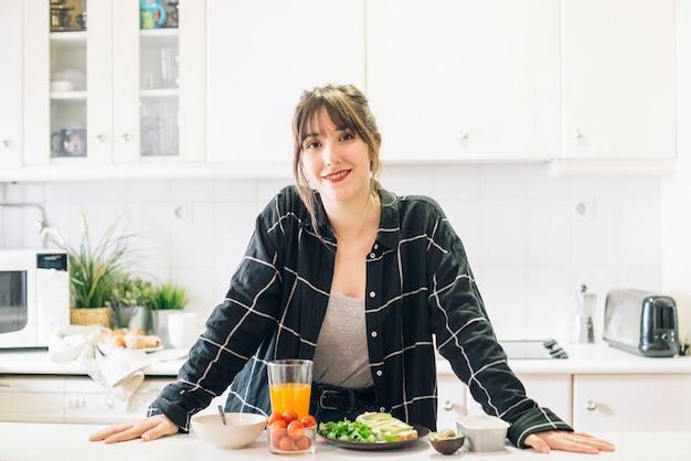 Retrato de una mujer feliz de pie en la cocina Foto gratis