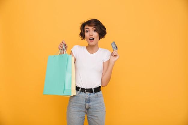 Retrato de una mujer feliz sorprendida sosteniendo bolsas de compras Foto gratis