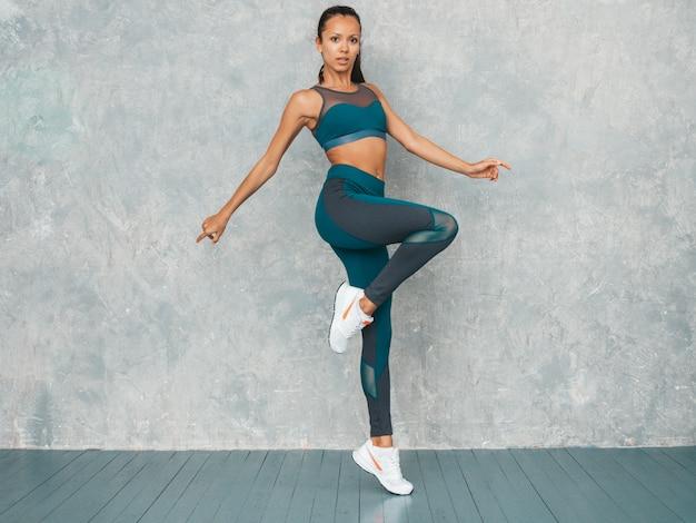 Retrato de mujer fitness en ropa deportiva buscando confianza. joven mujer vistiendo ropa deportiva. hermosa modelo con cuerpo bronceado perfecto. salto femenino en estudio cerca de la pared gris Foto gratis
