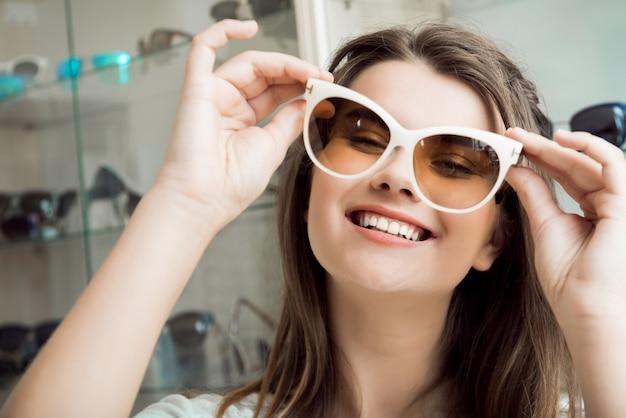 Retrato de mujer guapa en la tienda de óptica escogiendo un nuevo par de elegantes gafas de sol Foto gratis
