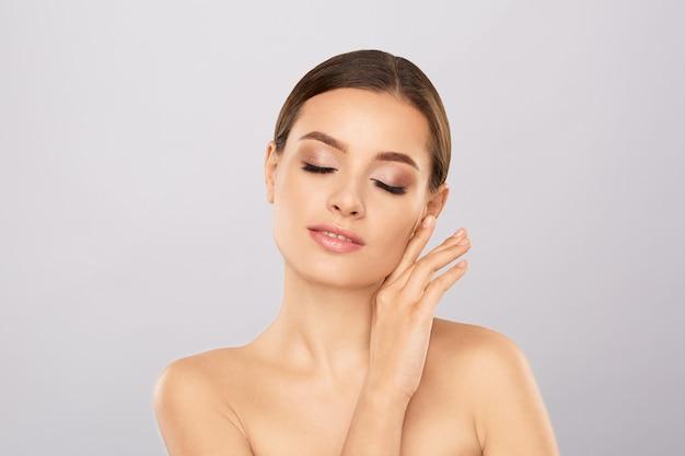 Retrato de mujer hermosa con maquillaje natural tocando su rostro. Foto Premium