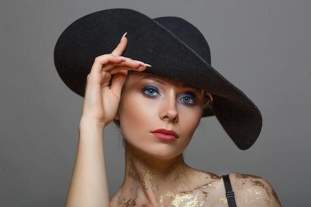 Retrato de mujer hermosa con maquillaje en sombrero negro sobre blanco, aislado Foto Premium