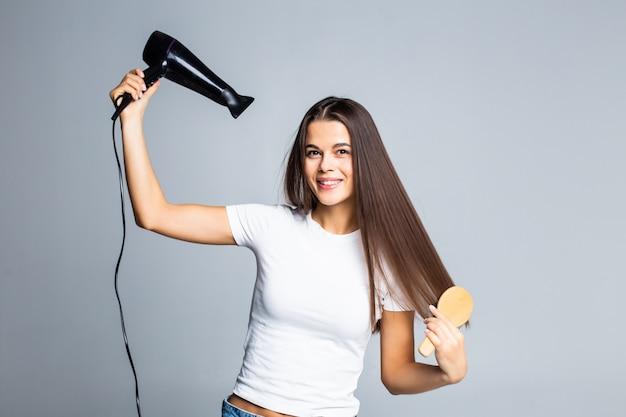 Retrato de mujer hermosa con secador de pelo aislado en gris Foto gratis