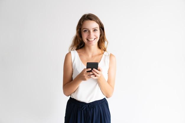 Retrato de la mujer joven alegre que se coloca y que usa el teléfono móvil. Foto gratis