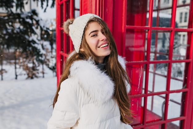 Retrato de mujer joven alegre en tejido gorro con pelo largo morena disfrutando del clima helado de invierno en la calle en el cuadro de teléfono rojo Foto gratis