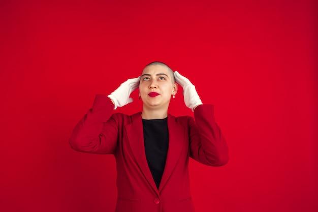 Retrato de mujer joven con aspecto extraño en la pared roja Foto gratis
